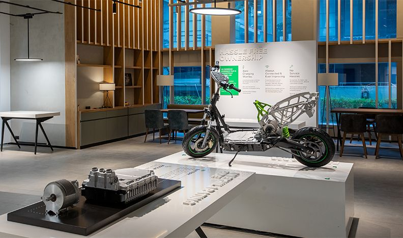 A stripped-down scooter is displayed on a platform inside the Ather showroom. A table in the foreground shows the motor assembly.