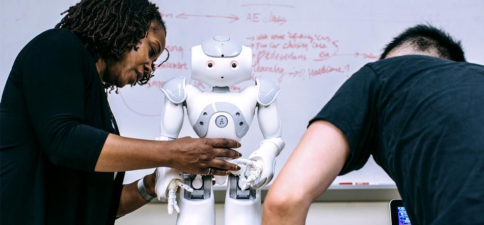 Dr. Howard holds the NAO robot while graduate student Jin Xu initializes the program on the laptop.